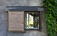 A metal-framed window is screened with a rustic rattan sliding blind