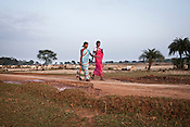 Village women walk past the vast land area that is proposed for a Tata Steel Plant and the local villagers are protesting against government  forcibly acquiring their village Sirisgura in Bastar district of Chattisgarh, India. Photo: Sanjit Das/Panos for The Times