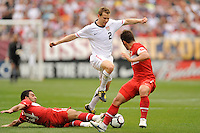 Jonathan Spector (2) of the United States jumps over a tackle by Arda Turan (14) of Turkey  during an international friendly between the men's national teams of the United States (USA) and Turkey (TUR) at Lincoln Financial Field in Philadelphia, PA, on May 29, 2010.