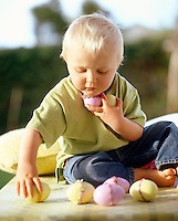 A toddler sitting on a table in the garden playing with his Easter eggs