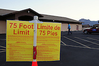 """Apache Junction, Arizona. November 6, 2012 - A bilingual """"75 Foot Limit"""" sign on a the parking lot next of Precinct 44 at a Moose Lodge chapter building in Apache Junction, Arizona warns people that only registered voters casting their vote are allowed within this limit. Photo by Eduardo Barraza © 2012"""