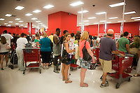 Shoppers on the check-out line at the new Target store in the East Harlem neighborhood of New York on its opening day, Sunday, July 25, 2010. Target, which is the second largest discount retailer in the United States has opened its first permanent Manhattan location in the East River Plaza, a vertical mall. The company has projected revenue of $90 million in the stores first year of operation (© Richard B. Levine).