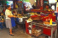 Mexican woman cooking tacos in the market in Tepoztlan, Morelos, Mexico. Tepoztlan has been designated a pueblo magico or magical town.