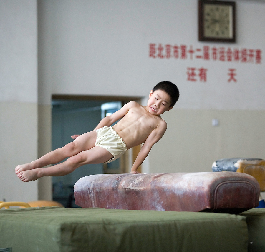 Eight year old Zhang Yu works on the pummel horse at a sports school to train gymnasts in Beijing.