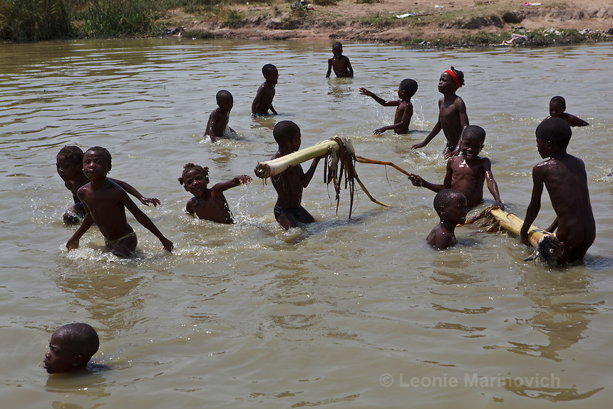 26 September 2011, Matala, Huila Province. Angola. This water hole serves the needs of both animals and humans, open defecation takes place on the edges, cows come for water, children bathe in it, wshing is done and water is collected for drinking purposes. A recipe for disaster. Deputy Administrator Castelho Marculino work with women in the community to provide and take care of essential water services. The administration of the municipality of Matala have been re-settling communities in strategic positions to this settlement on the outskirts of Matala. They have provided running water on tap at each household, latrines, washing areas and other essential services to the community.