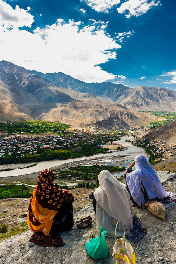 Three Muslim women sit on a rock overlooking the Suru River and the city of Kargil, Ladakh, Jammu and Kashmir State, India.
