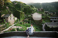 A tourists poses for photos at the abandoned fishing village of Hautouwan on the island of Shengshan July 25, 2015. Every day hundreds of tourists make their way on narrow footpaths between some of 500 houses covered by bewildered vegetation at Hautouwan, once home to over 2000 fishermen. The fishing village, a part of the Shengsi archipelago east of Shanghai was abandoned in early 90s and now only less than a half dozen people live there. REUTERS\Damir Sagolj