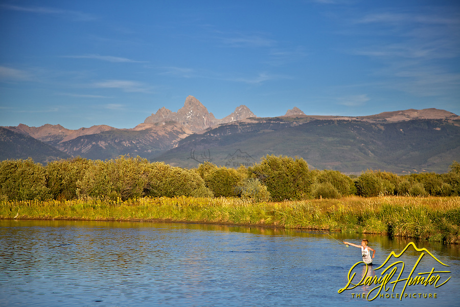 Boy fly-fishing the Teton River in Teton Valley Idaho. The Teton River meanders below the Grand Tetons in this beautiful valley.