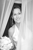 Black & white portrait of bride peering out window.