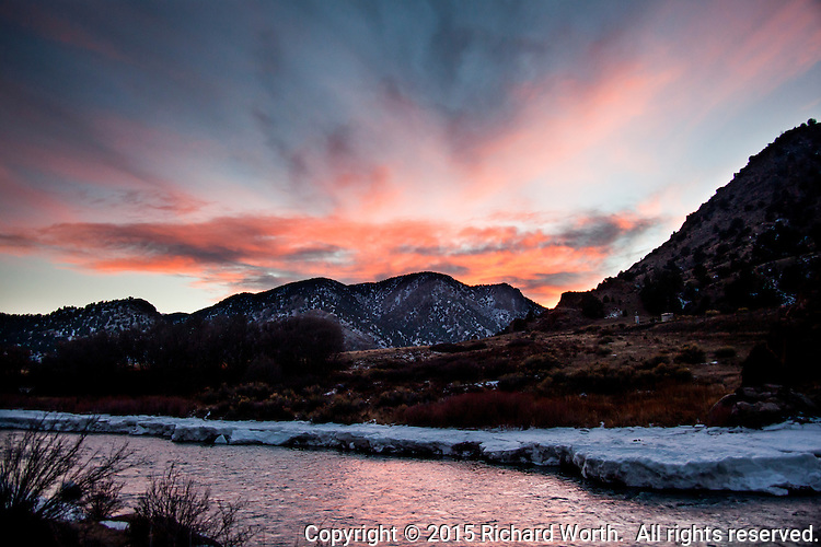 A winter sunset fills the sky and reflects in the water along the Arkansas River west of Canon City, Colorado.