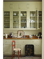 The cabinetry in the butler's pantry is painted in Ball Green by Farrow & Ball, the countertop is pine and the sink and fittings are by Waterworks