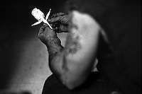 A convicted drug dealer and addict crafts tissue paper into a rose as he listens to a sermon at Joshua's Dream, a christian based rehabilitation center in Viper, Ky..