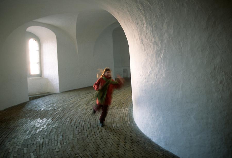 A girl in a red coat runs down the Round Tower ( Rundetårn) in Copenhagen, Denmark