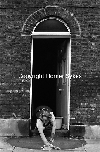 Woman cleaning her home and pavement. Waterloo SE London. England. 1975