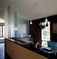 The contemporary kitchen is separated from the entrance hall by an opaque glass partition