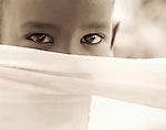 A young Fulani boy hides behind a veil in Ouagadougou, Burkina Faso.