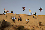 Palestinian youths practice their parkour skills in Gaza City on October 31, 2013. Parkour, French slang for the art of moving, is a physical activity that maximizes the body's efficiency with the aim of overcoming obstacles such as buildings, rails, and even people. Photo by Mohammed Asad