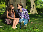 Young happy couple in their early thirties sitting on grass under a tree in a park