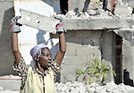Silvani Joseph, 48, survived the January 12, 2010, earthquake and carries debris as she and her neighbors begin to build temporary shelters in the Port-au-Prince neighborhood of Belair.
