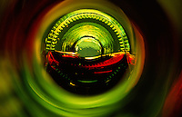 """Beauty at the Bottom: Red Wine 1""- This image is a photograph of a wine bottle shot right down the mouth of the bottle. A television provides the main light source"
