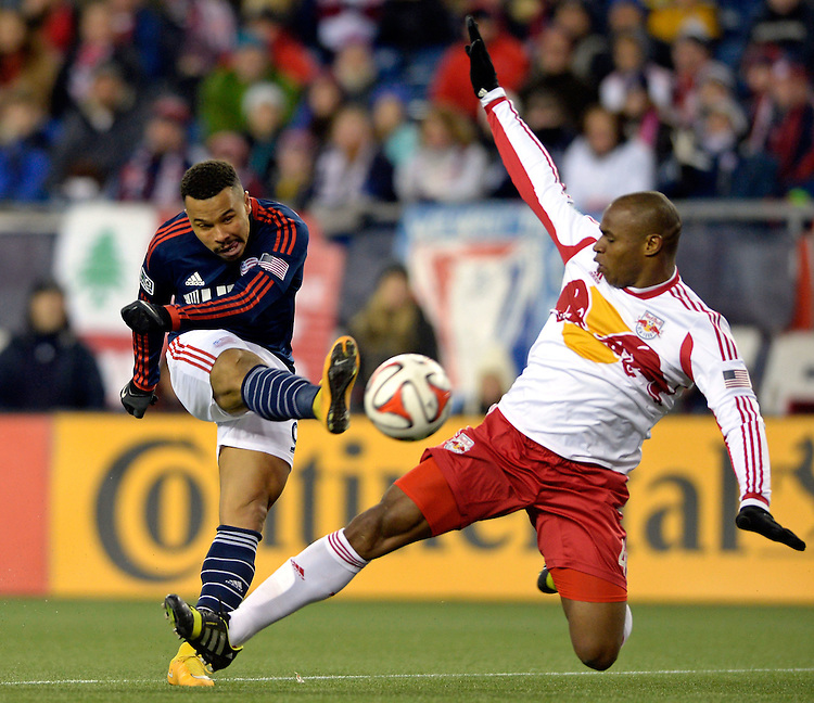 New England Revolution forward Charlie Davies, left, shoots the ball past New York Red Bulls defender Jamison Olave during the second half of Major League Soccer's Eastern Conference championship at Gillette Stadium on Saturday, November 29, 2014. Photo by Christopher Evans
