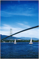 Two sailboats racing under the Lions Gate Bridge with North Vancouver in the background, taken from the seawall in Stanley Park, Vancouver, BC.