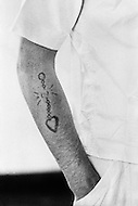 Cummins, AR - February 3rd 1968<br /> Cummins unit of Arkansas State Penitentiary. The corruption scandal of the historical penitentiary inspired the 1980 film Brubaker, which chronicled the warden's inside investigation into the corrupt southern prison system. The prison raise their own pigs. Close up of tatoo of a white prisioner.<br /> Cummins, Arkansas. 3 f&eacute;vrier 1968.<br /> Gros plan d'un tatouage fait &agrave; la prison sur le bras d'un jeune prisonier.