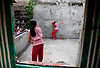 Two Filipino children play dodgeball in an abandoned house in Manila.
