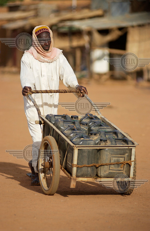 A man pushes a cart filled with water jugs.