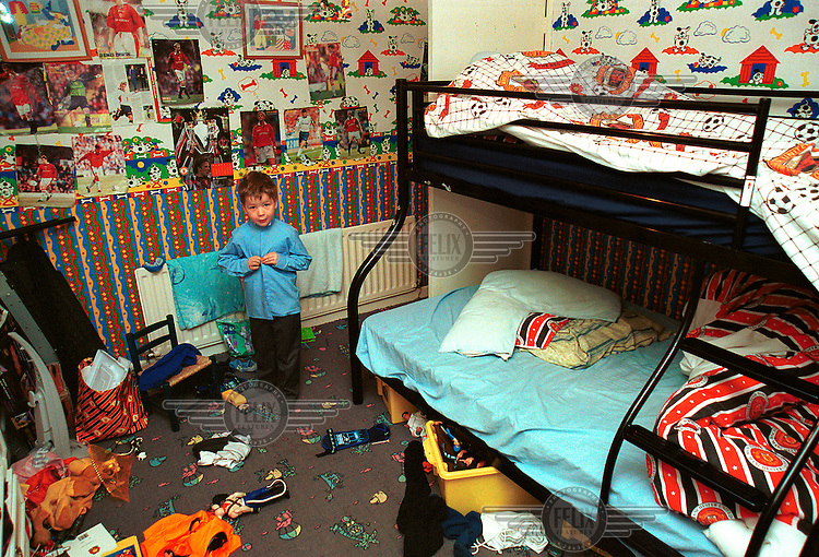 Five-year-old Joseph gets dressed for school in his bedroom, which is adorned with Manchester United football memorabilia.