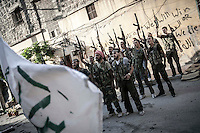 Rebel fighters belonging to the Kateba Omar Ben Abdul Aziz shout victory slogans as they celebrate a successful military operation to push back the Assad troops from the first line of fire in Aamria battlefield at the southwest of Aleppo City.