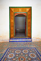 Berber Arabesque painted wood door surround and Zellige tile floor.The Petite Court, Bahia Palace, Marrakesh, Morroco