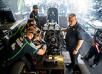 Feb 10, 2017; Pomona, CA, USA; Crew members surround the car of NHRA funny car driver Alexis DeJoria as she warms up in the pits during qualifying for the Winternationals at Auto Club Raceway at Pomona. Mandatory Credit: Mark J. Rebilas-USA TODAY Sports