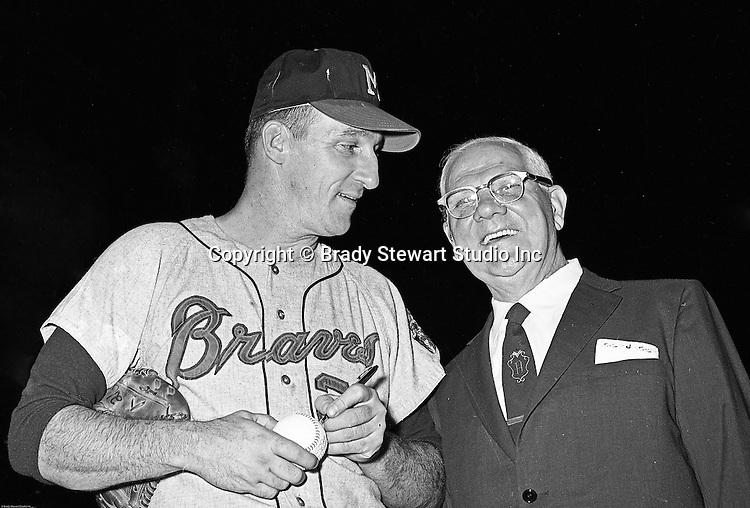 Pittsburgh PA: View of Warren Spahn signing an autograph baseball for a local businessman at the annual HYPO game at Forbes Field - 1965.<br />