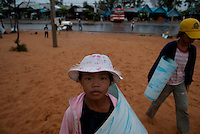 A Vietnamese girl waits for tourists to sell a sliding ride down sand dunes in Mui Ne.  Mui Ne is famous for its red and white sand dunes.
