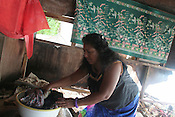 Mrs Tiaon Bwere, of Betio village, rescues clothes from her house which was smashed the previous day by the 'king tides' which this week came ashore on the South Pacific island of Kiribati. Her property was damaged by the large waves, and she and her husband now face the prospect of rebuildign their home. They wish to seek assistance from the government of Kiribati.