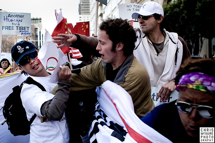 A Chinese supporter, left, stands in the way of a group of marchers carrying a banner in protest of China's involvement with the Olympics near San Francisco's Ferry Building on Wednesday, April 9, 2008.  The Olympic Torch was supposed to be carried past the Ferry Building, but organizers altered the course at the last minute, leaving thousands of people upset.  (Christopher McGuire)