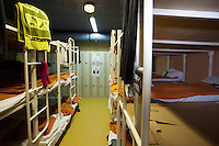 Switzerland. Geneva. Women dormitory with triple bunk metal beds in the fallout shelter Richemont. Clothes and casual clothes from Romani women are hanged on beds' structures. The bunker was constructed as civil defense measures during the Cold War and is a unit of the Civil Protection. Switzerland is unique in having enough nuclear fallout shelters to accommodate its entire population. Romani are widely known by the exonym Gypsies (or Gipsies) and also as Romany, Romanies, Romanis, Roma or Roms. 7.02.2014 © 2014 Didier Ruef
