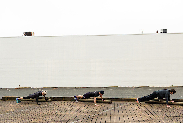 December 22, 2014. Lexington, North Carolina.<br />  (left to right) Nicole Smith, Mayor Newell Clark and Frank Callicutt use parking blocks to perform pushups as part of their around town workout routine.<br />   Newell Clark, the 43 year old mayor of Lexington, NC, leads a group of friends and colleagues on a 4 times a week exercise routine around downtown. The group uses existing infrastructure, such as an abandoned furniture factory, loading docks, stairs, and handrails to get fit and increase awareness of healthy lifestyles in a town more known for BBQ.<br /> Jeremy M. Lange for the Wall Street Journal<br /> Workout_Clark