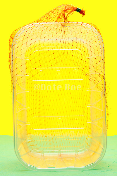 empty fruit basket with orange net object on yellow green background