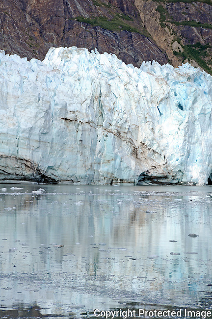 close up of Marjorie glacier, and it's reflection, in the calm blue waters of Glacier Bay