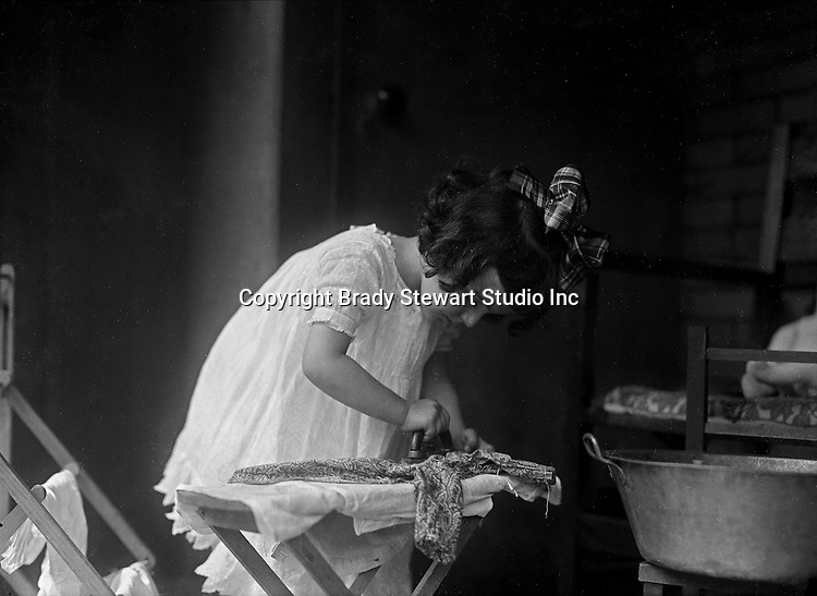 Products:  Children's Ironing Board, iron, was pan and clothes hanger<br /> <br /> Wilkinsburg PA:  Helen Stewart ironing her dolls clothes just like mom.