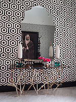 The walls of the entrance hall are covered in a Hexagon wallpaper by Cole & Son and it is furnished with a 'Twig' brass console table beneath a custom designed frameless mirror, both designed and produced by Hall. The floor is Carrara marble