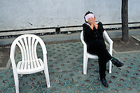 China. Province of Beijing. Beijing. A woman seated on a white plastic chair takes a nap.  © 2004 Didier Ruef