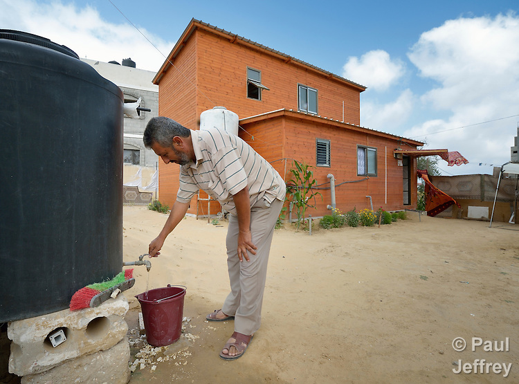 Abed Rabu Abu Jowe'a fills a bucket with water to irrigate the flowers he planted in front of his family's transitional house built by Catholic Relief Services in Khan Yunis, Gaza. His house and many others in the area were destroyed by the Israeli military during the 2014 war between the state of Israel and the Hamas government of Gaza. His family of 11 people moved into the new 80-square meter house in April 2015. A taxi driver, he has already added to the house, and says that with proper care it should last at least ten years, twice what CRS expects. Yet Jowe'a isn't hopeful that tensions between Israel and Gaza will diminish anytime soon.