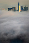 Fog slides into the Bay Area of San Francisco with just the taller building shows through.