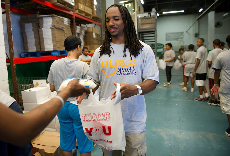"UNITED STATES - JUNE 21: Cleveland Browns free safety and D.C. native Usama Young (C) helps prepare lunch bags with local school kids for the Capital Area Food Bank ""Weekend Bag Program,"" which provides bags of food to 1,000 children weekly when they do not have access to school meals during summer months. Young sponsors a youth foundation that runs a football camp and afterschool activities. (Photo by Chris Maddaloni/CQ Roll Call)"