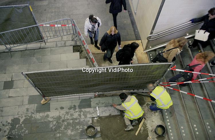 Foto: vidiPhoto..NIJMEGEN - Personeel van aannemer Welling plaatst in opdracht van ProRail nieuwe tegels in de voetgangerstunnel onder het Centraal Station in Nijmegen. Een jaar geleden bleek dat de reizigers in de nieuwe tunnel grote kans liepen een flinke smak te maken. Borden waarschuwden de reizigers de afgelopen tijd voor gladheid. Bovendien werden er stukken vloerkleed neergelegd. Nog steeds is niet duidelijk hoe het komt dat reizigers uitgleden. Exact dezelfde bestrating ligt in de stationshal en daar zijn geen problemen.