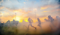 Photo by Gary Cosby Jr. Hartselle High players run onto the field in front of the setting sun and through a cloud of generated smoke for Hartselle Game with Hayden Friday night at J.P. Cain Stadium in Hartselle.