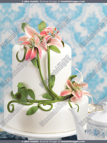 Fancy cake decorated with lilies on a table
